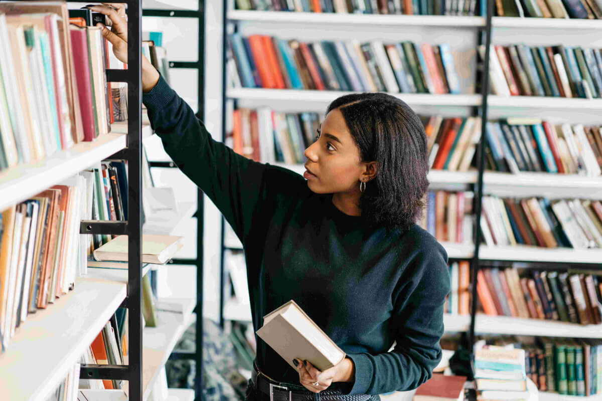 Woman grabbing a book from the shelf.